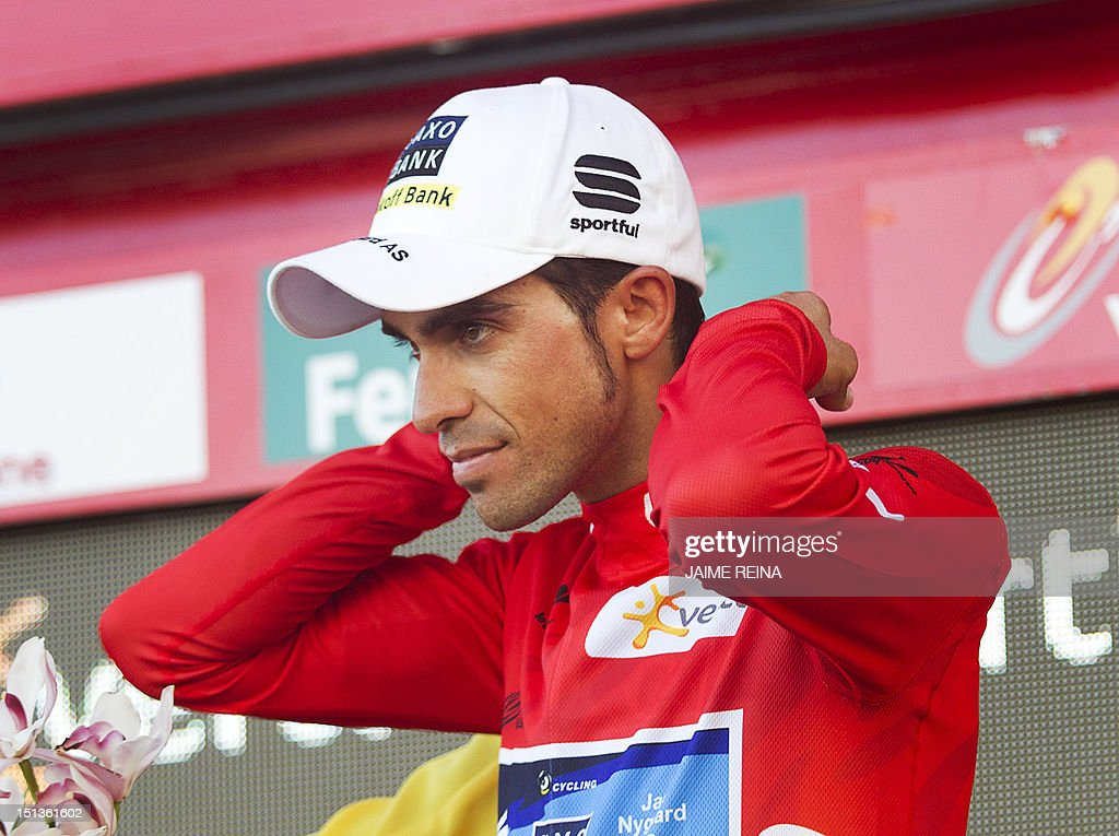 Spain's Alberto Contador of the Saxo Bank-Tinkoff Bank Team celebrates on the podium after retaining the leader's red jersey at the end of the eighteenth stage of the Vuelta tour of Spain, a 204,5 kms ride from Aguilar de Campoo to Valladolid, on September 6, 2012. AFP PHOTO / Jaime REINA