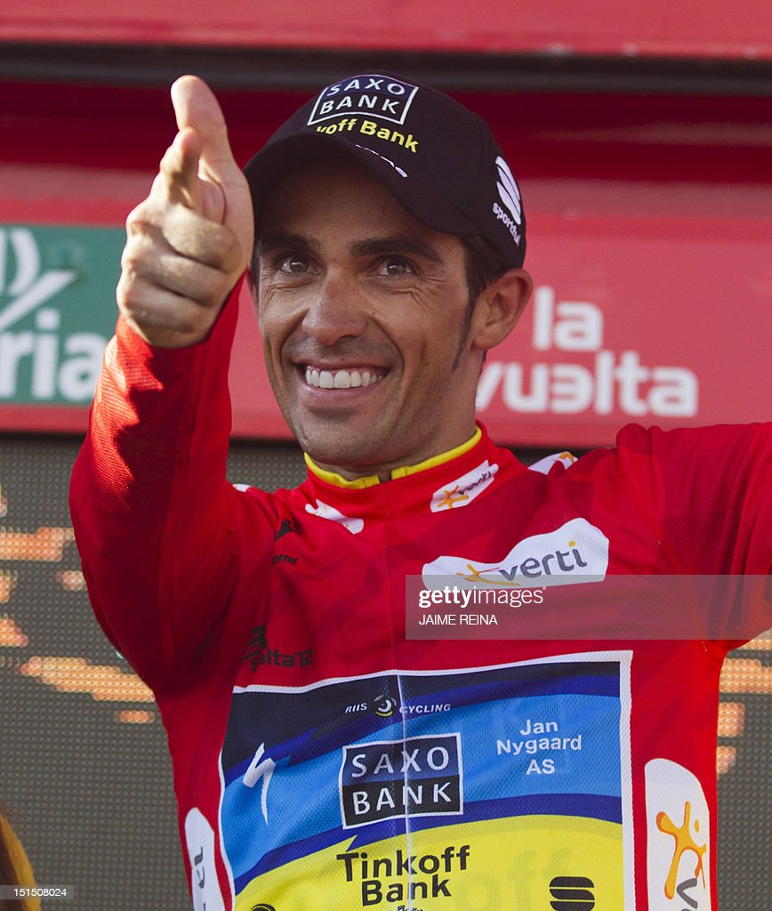 Spain's Alberto Contador of the Saxo Bank-Tinkoff Bank Team celebrates on the podium after retaining the leader's red jersey at the end of the 20th stage of the Vuelta tour of Spain, a 170,7 kms ride from La Faisanera golf to Bola del Mundo, on September 8, 2012 in Navacerrada. Russia's Denis Menchov of the Katusha team won the 20th and penultimate stage of the Tour of Spain with Spain's Alberto Contador retaining the overall lead. AFP PHOTO/ Jaime REINA
