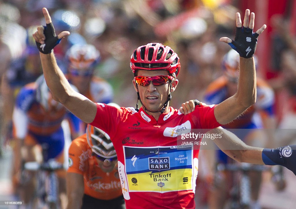 Spain's Alberto Contador (C) of the Saxo Bank-Tinkoff Bank Team celebrates while crossing the finish line of the Vuelta cycling Tour of Spain in Madrid, on September 9, 2012. Spain's Alberto Contador, racing his first Grand Tour since returning from a two-year doping ban last month, won his second Tour of Spain crown, Spain's Alejandro Valverde of the Movistar team was second and compatriot Joaquim Rodriguez of Katusha team third . AFP PHOTO/ Jaime REINA