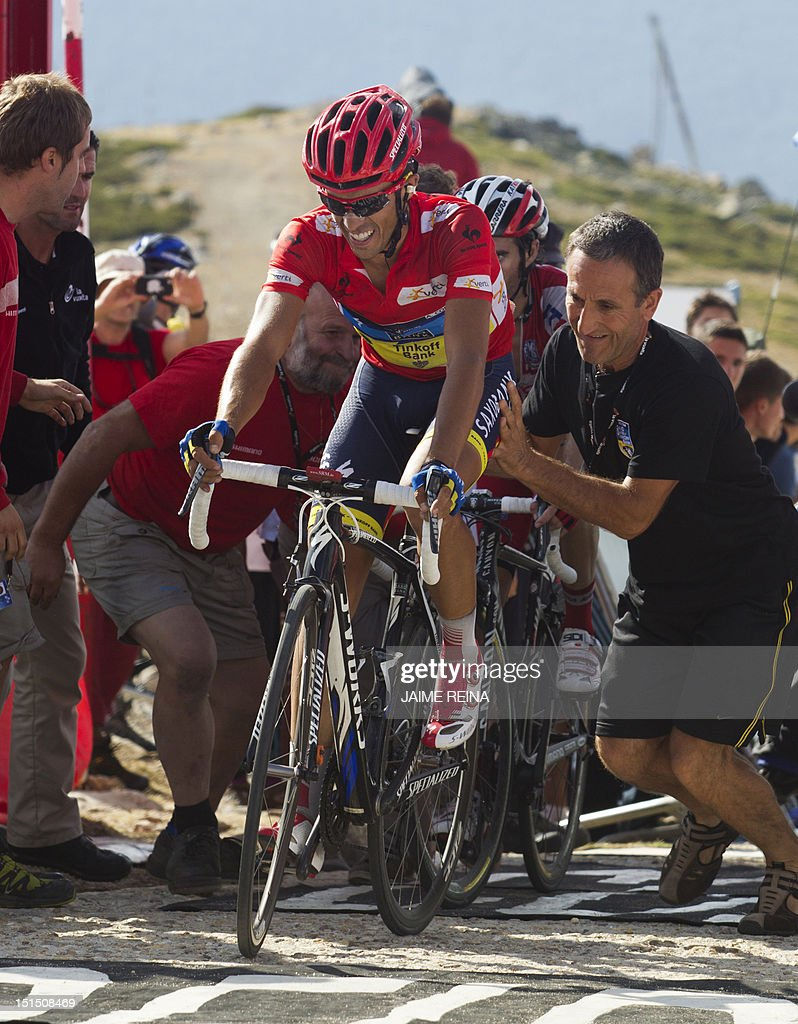Spain's Alberto Contador of the Saxo Bank-Tinkoff Bank Team is pushed by supporters on the finish line of the 20th stage of the Vuelta tour of Spain, a 170,7 kms ride from La Faisanera golf to Bola del Mundo, on September 8, 2012 in Navacerrada. Russia's Denis Menchov of the Katusha team won the 20th and penultimate stage of the Tour of Spain with Spain's Alberto Contador retaining the overall lead. AFP PHOTO/ Jaime REINA