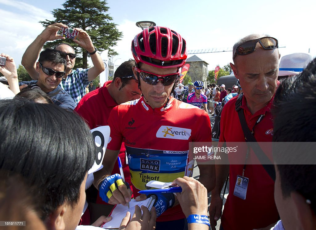 Spain's Alberto Contador of the Saxo Bank-Tinkoff Bank Team signs autographs during the 20th stage of the Vuelta tour of Spain, a 170,7 kms ride from La Faisanera golf to Bola del Mundo, on September 8, 2012 in Navacerrada. Russia's Denis Menchov of the Katusha team won the 20th and penultimate stage of the Tour of Spain with Spain's Alberto Contador retaining the overall lead. AFP PHOTO/ Jaime REINA