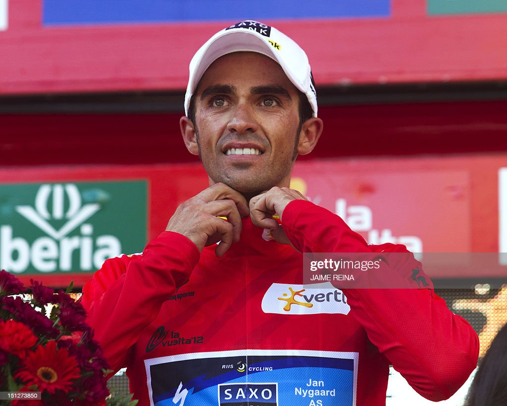 Spain's Alberto Contador of the Saxo Bank-Tinkoff Bank Team smiles on the podium with his new leader's red jersey at the end of the seventeenth stage of the Vuelta tour of Spain, a 187,3 kms ride from Santander to Fuente De on September 5, 2012. AFP PHOTO/ Jaime REINA