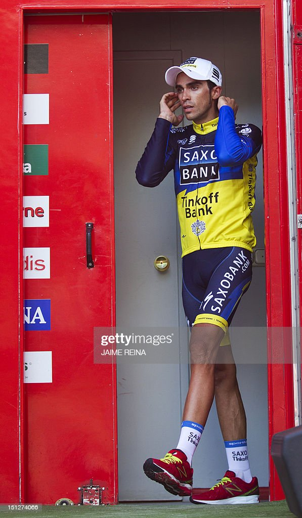Spain's Alberto Contador of the Saxo Bank-Tinkoff Bank Team walks onto the podium after acquiring the leader's red jersey at the end of the seventeenth stage of the Vuelta tour of Spain, a 187,3 kms ride from Santander to Fuente De on September 5, 2012. AFP PHOTO/ Jaime REINA