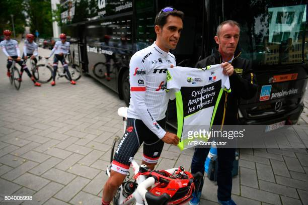 Spain's Alberto Contador poses for photographers holding a jersey reading ' Cyclists respect the rules ' prior to a training session in Dusseldorf...