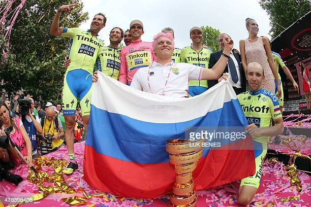 Spain's Alberto Contador poses with his trophy flanked by his TinkoffSaxo teammates and Russian businessman and team sponsor Oleg Tinkov holding a...