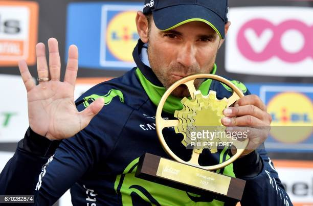 Spain's Alejandro Valverde of the Movistar team celebrates as he kisses the trophy during the podium ceremony in Mur de Huy after winning and...