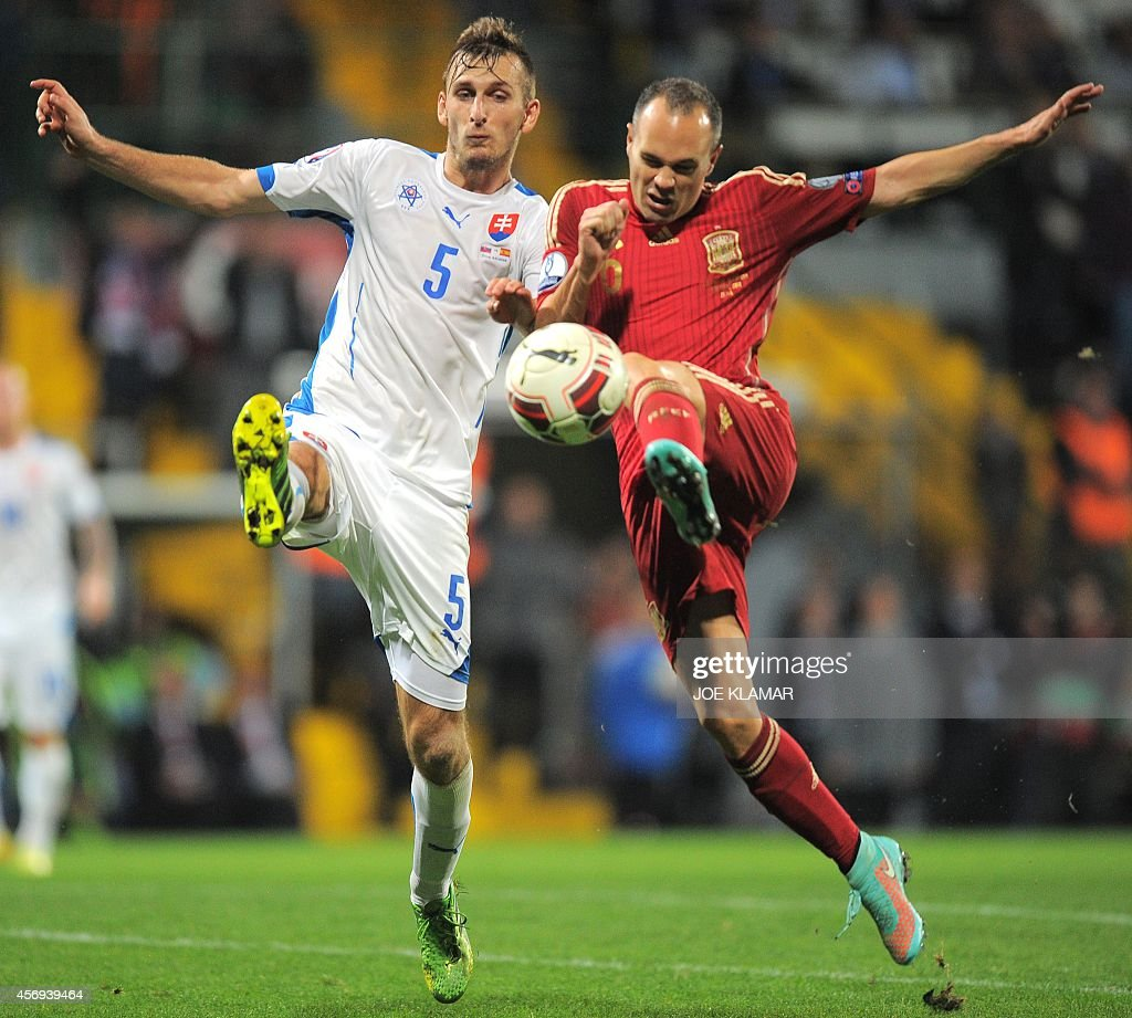 Spain's Andres Iniesta and Slovakia's Norbert Gyomberfight for a ball during Euro 2016 qualifing football match between Slovakia and Spain in...
