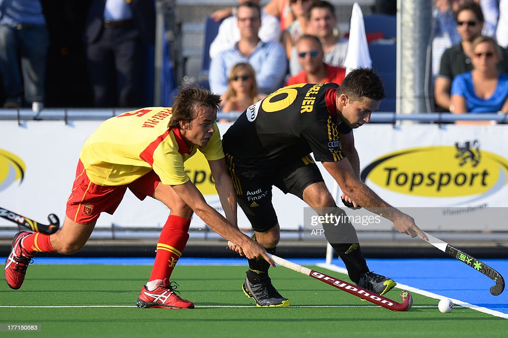 Spain's Bosco Perez-Pla De Alvear (L) fights for the ball with Belgium's Cedric Charlier during the match between Belgium and Spain, in the Men Pool A at the European Field Hockey Championships 2013 on August 21, 2013, at the Braxgata hockey club in Boom.