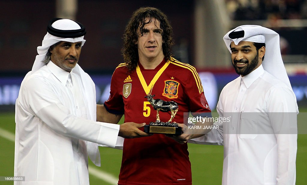 Spain's Carles Puyol (C) receives a trophy for his 100th international match from Qatari Football Association president Sheikh Hamad bin Khalifa al-Thani (L) and Hassan al-Thawadi, secretary-general of the supreme committee of the 2022 FIFA World Cup in Qatar, after the international friendly football match between Spain and Uruguay at the Khalifa International Stadium in the Qatari capital Doha on February 6, 2013.