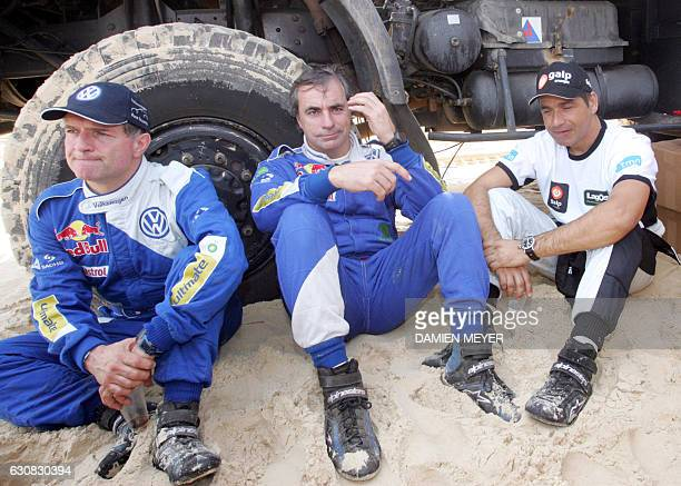 Spain's Carlos Sainz flanked by French codriver Michel Perin and Portugal's Carlos Sousa wait on a Dakar beach for the start of the 15th and final...