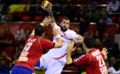 Spain's centre back Joan Canellas vies with Serbia's left back Momir Ilic and Serbia's centre back Nenad Vuckovic during the 23rd Men's Handball...