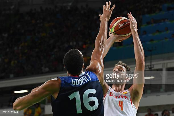 TOPSHOT Spain's centre Pau Gasol tries to score by France's centre Rudy Gobert during a Men's quarterfinal basketball match between Spain and France...