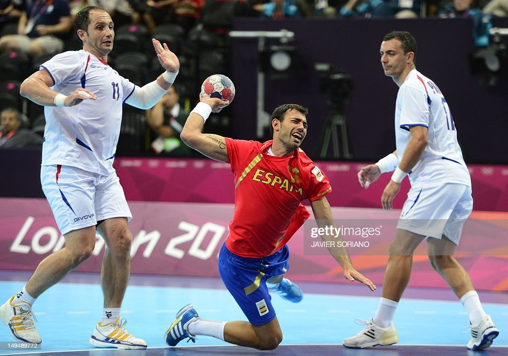 Spain's centreback Daniel Sarmiento Melian (C) jumps to shoot past Serbia's Alem Toskic (L) and Serbia's Rajko Prodanovic during the men's preliminaries Group B handball match Spain vs Serbia for the London 2012 Olympics Games on July 29, 2012 at the Copper Box hall in London.