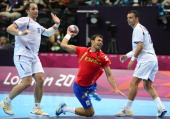 Spain's centreback Daniel Sarmiento Melian jumps to shoot past Serbia's Alem Toskic and Serbia's Rajko Prodanovic during the men's preliminaries...