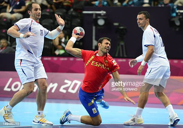 Spain's centreback Daniel Sarmiento Melian jumps to shoot past Serbia's Alem Toskic and Serbia's Rajko Prodanovic during the men's preliminaries...