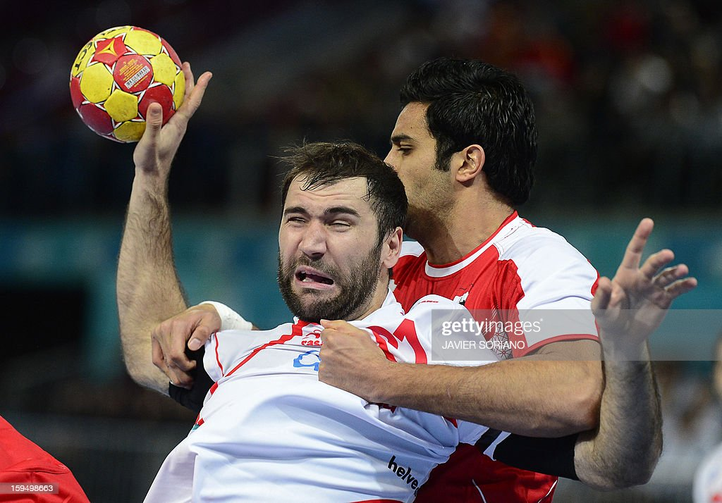 Spain's centreback Joan Canellas (L) vies with Egypt's centreback Islam Hassan (R) during the 23rd Men's Handball World Championships preliminary round Group D match Egypt vs Spain at the Caja Magica in Madrid on January 14, 2013.