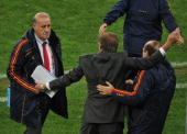 Spain's coach Vicente Del Bosque looks on as team members celebrate in the 2010 World Cup semifinal football match between Germany and Spain on July...