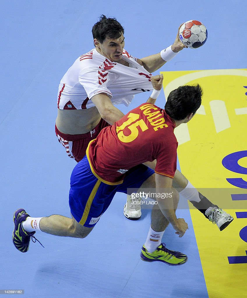 Spain's Cristian Ugalde Garcia (down) vies with Poland's Krzysztof Lijewski (up) during the handball pre-Olympic qualifying match Spain vs Poland on April 8, 2012 at the Tecnificacion Center sports hall in Alicante.