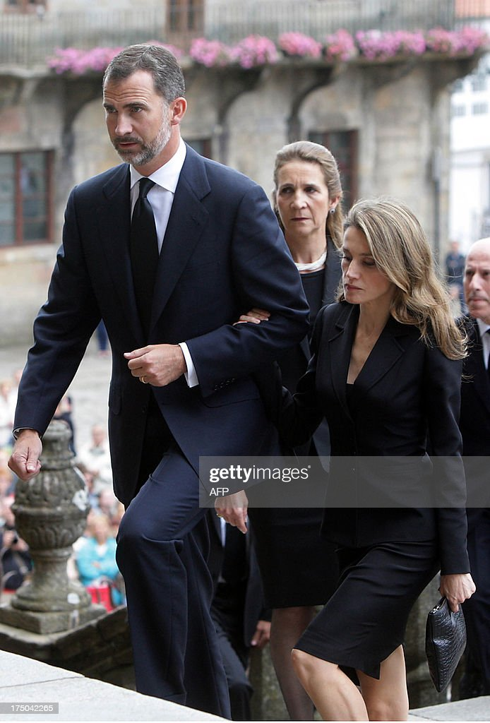 Spain's Crown Prince Felipe (L) and Spain's Princess Letizia (C) arrive followed by Spain's Infanta Elena arrive to attend a a memorial service for the victims the derailed train of Angrois, at the cathedral of Santiago de Compostela on July 29, 2013. The driver of a train that hurtled off the rails in Spain was charged on July 28 with 79 counts of reckless homicide and released on bail after being questioned by a judge.