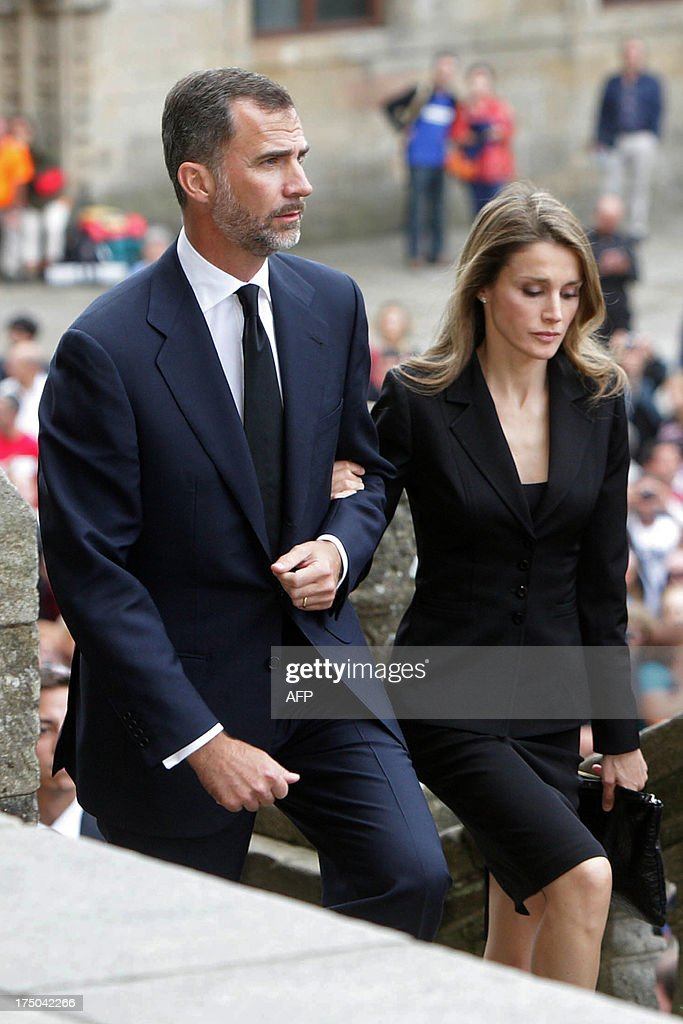 Spain's Crown Prince Felipe (L) and Spain's Princess Letizia (C) arrive to attend a a memorial service for the victims the derailed train of Angrois, at the cathedral of Santiago de Compostela on July 29, 2013. The driver of a train that hurtled off the rails in Spain was charged on July 28 with 79 counts of reckless homicide and released on bail after being questioned by a judge.