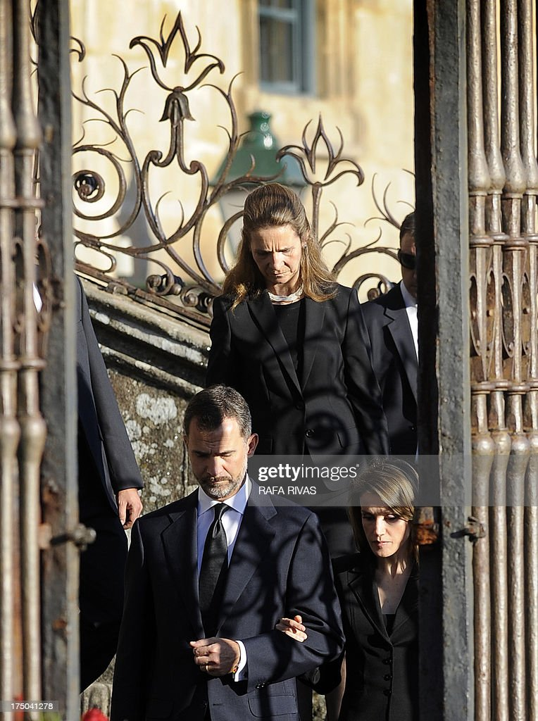 Spain's Crown Prince Felipe (L) and Spain's Princess Letizia (R) followed by Spain's Infanta Elena leave a memorial service for the victims the derailed train of Angrois, at the cathedral of Santiago de Compostela on July 29, 2013. The driver of a train that hurtled off the rails in Spain was charged on July 28 with 79 counts of reckless homicide and released on bail after being questioned by a judge.