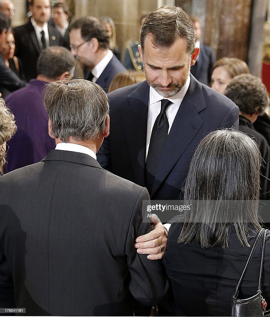 Spain's Crown Prince Felipe comforts relatives of the victims after a memorial service for the victims the derailed train of Angrois, at the cathedral of Santiago de Compostela on July 29, 2013. The driver of a train that hurtled off the rails in Spain was charged on July 28 with 79 counts of reckless homicide and released on bail after being questioned by a judge. AFP PHOTO/ POOL/ LAVANDEIRA JR