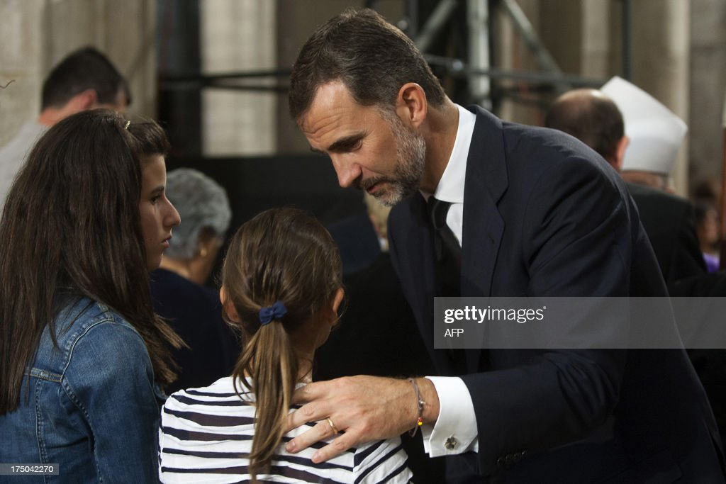 Spain's Crown Prince Felipe comforts relatives of the victims at the end of a memorial service for the victims the derailed train of Angrois, at the cathedral of Santiago de Compostela on July 29, 2013. The driver of a train that hurtled off the rails in Spain was charged on July 28 with 79 counts of reckless homicide and released on bail after being questioned by a judge.