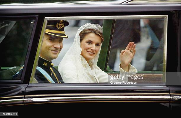 Spain's Crown Prince Felipe de Bourbon and his bride Letizia Ortiz wave from their limousine after their wedding ceremony May 22 2004 in Madrid
