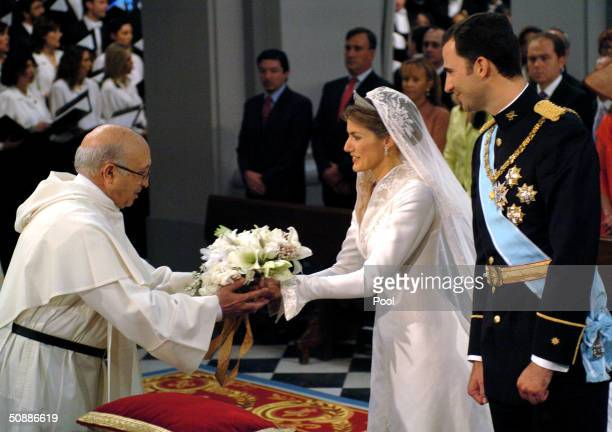 Spain's Crown Prince Felipe de Bourbon stands next to bride Letizia Ortiz as she offers her wedding bouquet in memory of the victims of March 11 at...