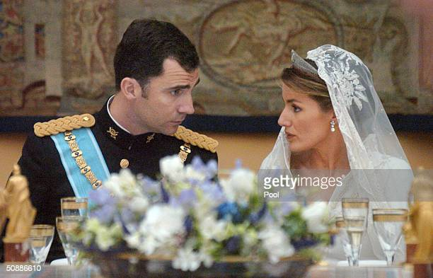 Spain's Crown Prince Felipe de Bourbon talks to his bride Princess Letizia Ortiz during their wedding banquet at the royal palace May 22 2004 in...
