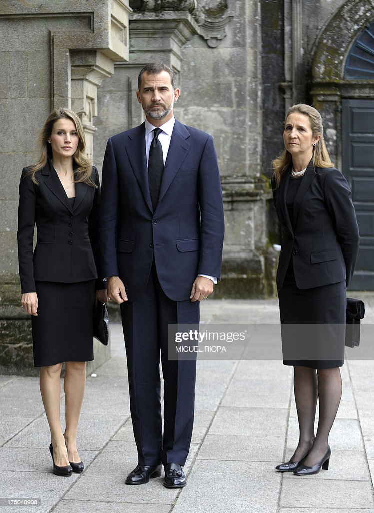 Spain's Crown Prince Felipe (C), Spain's Princess Letizia (L) and Spain's Infanta Elena pose as they arrive to attend a memorial service for the victims the derailed train of Angrois, at the cathedral of Santiago de Compostela on July 29, 2013. The driver of a train that hurtled off the rails in Spain was charged on July 28 with 79 counts of reckless homicide and released on bail after being questioned by a judge. AFP PHOTO/ POOL/ MIGUEL RIOPA