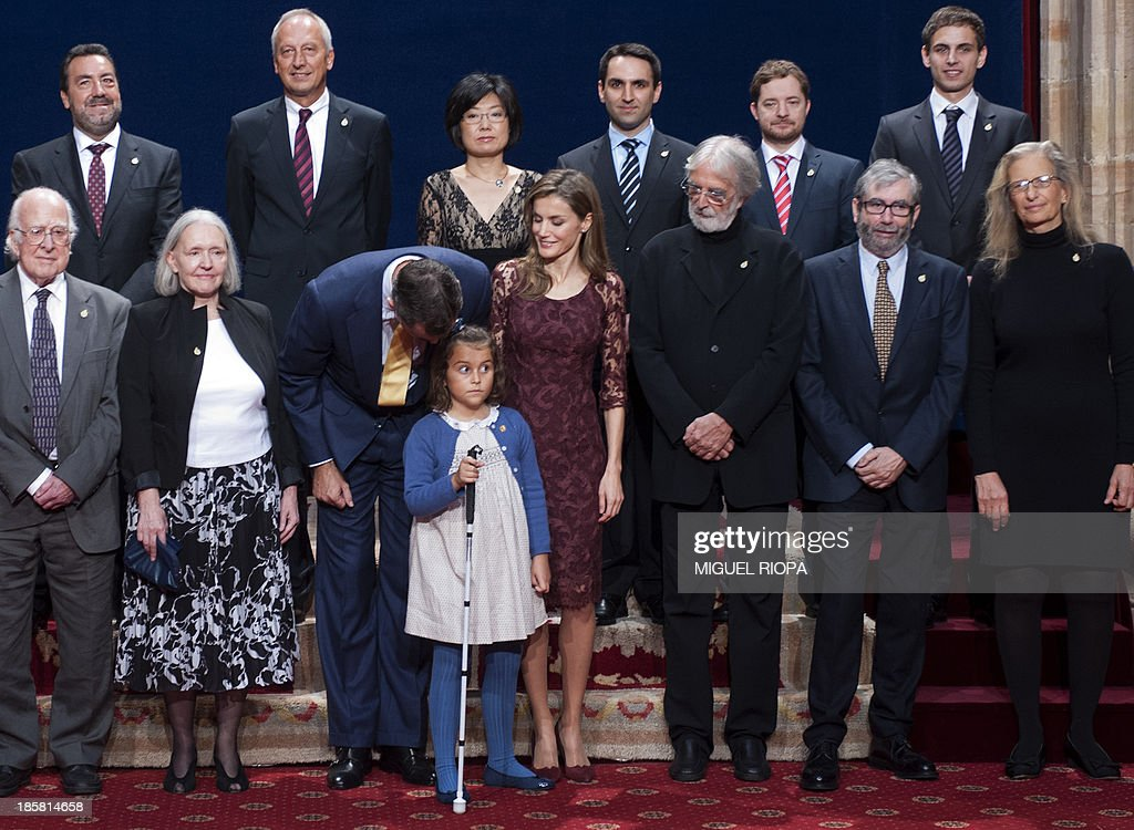 Spain's Crown Prince Felipe (3rd L) talks to a blind girl as he poses with Princess Letizia (C) and the 2013 Prince of Asturias Award laureates, (L-R) US photographer Annie Leibovitz, Spanish writer Antonio Munoz Molina, Austrian director Michael Haneke, Dutch-American sociologist Saskia Sassen, British scientist Peter Higgs and Belgian scientist Francois Englert at the Reconquista Hotel of the northern Spanish city of Oviedo on October 25, 2013.