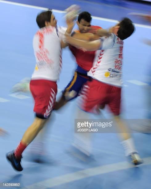 Spain's Daniel Sarmiento Melian vies with Serbians Nikola Manojlovic and Alem Toskic during the handball preOlympic qualifying match Spain vs Serbia...