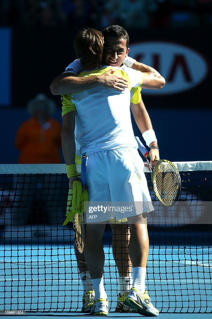 Spain's David Ferrer (L) embraces after victory in his men's singles match against compatriot Nicolas Almagro on the nineth day of the Australian Open tennis tournament in Melbourne on January 22, 2013. AFP PHOTO/LUCAS DAWSON /POOL IMAGE STRICTLY RESTRICTED TO EDITORIAL USE - STRICTLY NO COMMERCIAL USE