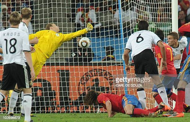 Spain's defender Carles Puyol heads the ball to score Spain's opening goal past Germany's goalkeeper Manuel Neuer during the 2010 World Cup semifinal...