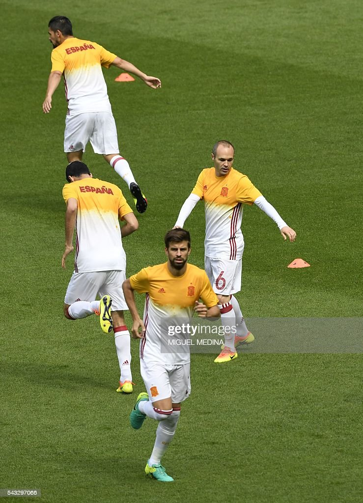 Spain's defender Gerard Pique (bottom) and Spain's midfielder Andres Iniesta (R) warm up with teammates before the Euro 2016 round of 16 football match between Italy and Spain at the Stade de France stadium in Saint-Denis, near Paris, on June 27, 2016. / AFP / MIGUEL