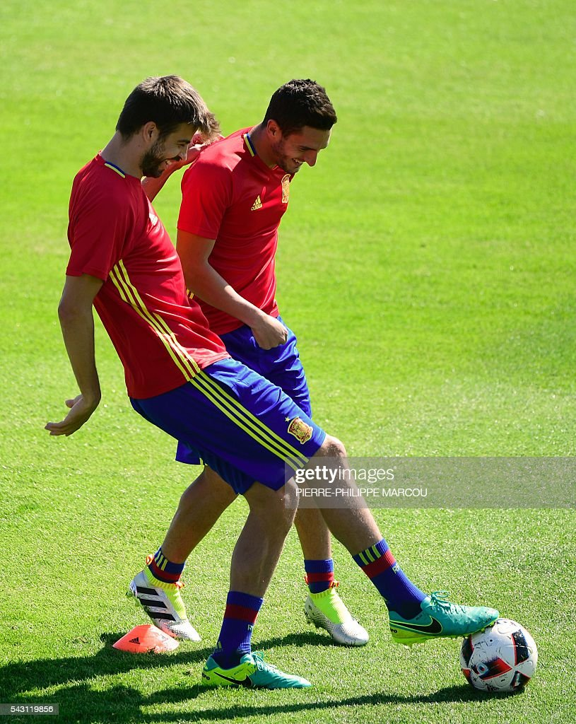 Spain's defender Gerard Pique (L) and Spain's midfielder Koke attend a training session at Saint Martin de Re's stadium on June 26, 2016, on the eve of their match against Italy during the Euro 2016 football tournament. / AFP / PIERRE