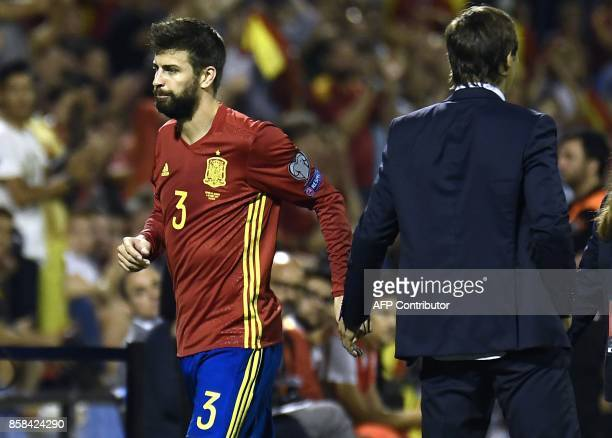 Spain's defender Gerard Pique cheers Spain's coach Julen Lopetegui as he leaves the field during the World Cup 2018 qualifier football match Spain vs...