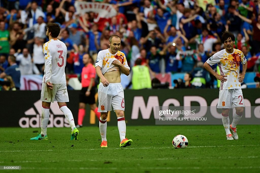 Spain's defender Gerard Pique, Spain's midfielder Andres Iniesta and Spain's midfielder David Silva react after the Euro 2016 round of 16 football match between Italy and Spain at the Stade de France stadium in Saint-Denis, near Paris, on June 27, 2016. MARCOU