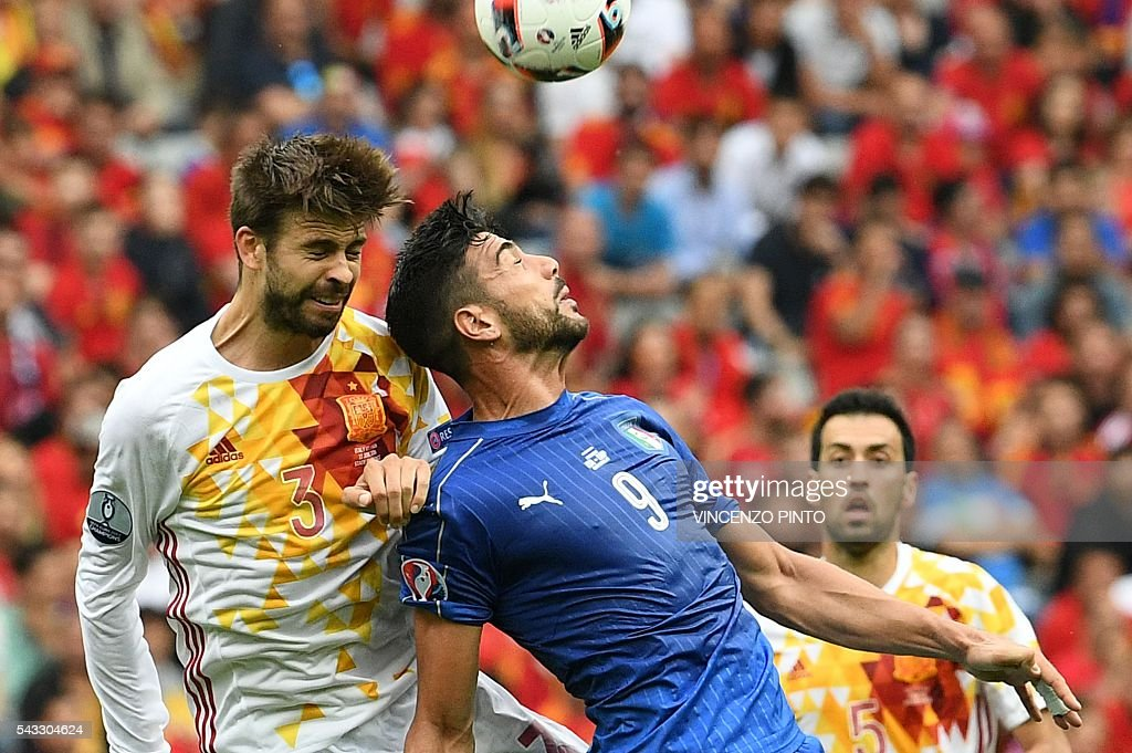Spain's defender Gerard Pique (L) vies for the ball with Italy's forward Pelle during the Euro 2016 round of 16 football match between Italy and Spain at the Stade de France stadium in Saint-Denis, near Paris, on June 27, 2016. / AFP / VINCENZO