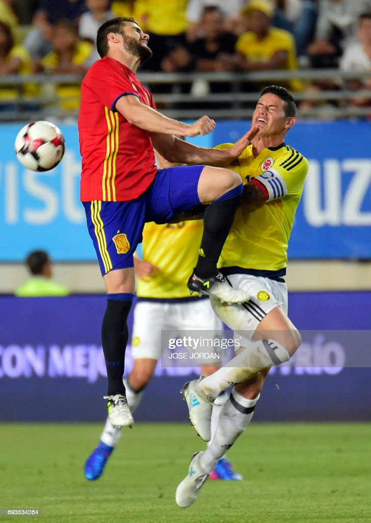 Spain's defender Ignacio Fernandez (L) vies with Colombia's midfielder James Rodriguez during the friendly international football match Spain vs Colombia at the Condomina stadium in Murcia on June 7, 2017. /