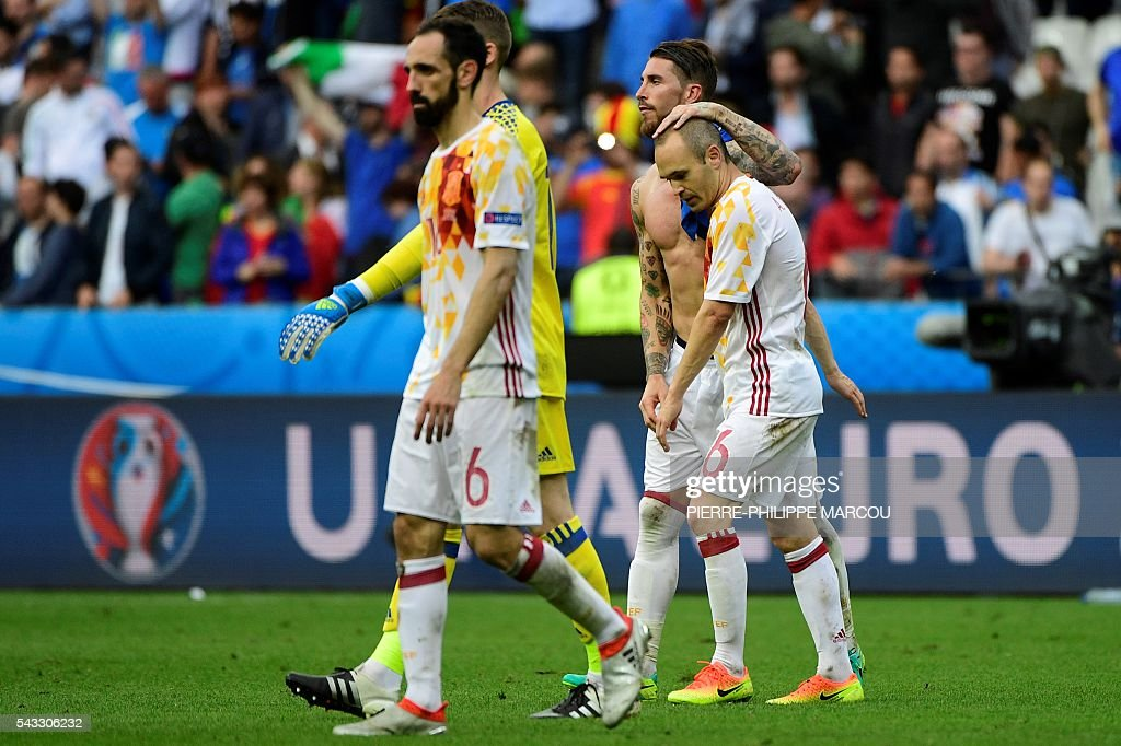 Spain's defender Juanfran, Spain's defender Sergio Ramos and Spain's midfielder Andres Iniesta react after the Euro 2016 round of 16 football match between Italy and Spain at the Stade de France stadium in Saint-Denis, near Paris, on June 27, 2016. MARCOU