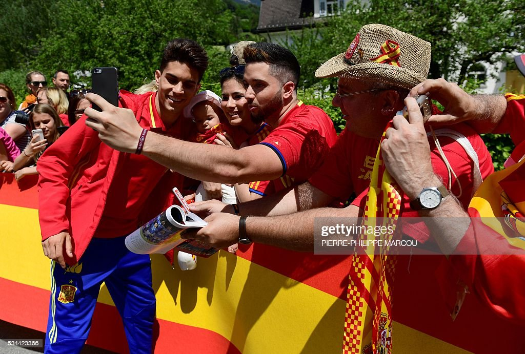 Spain's defender Marc Batra (L) poses with fans as he arrives at his hotel in Schruns on May 26, 2016 where the team will train for the upcoming Euro 2016 European football championships. / AFP / PIERRE