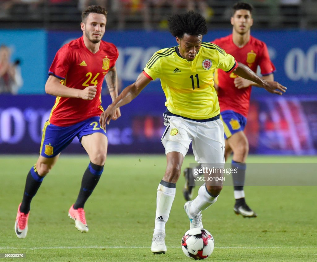 Spain's defender Saul Niguez (L) vies with Colombia's midfielder Juan Cuadrado during the friendly international football match Spain vs Colombia at the Condomina stadium in Murcia on June 7, 2017. /