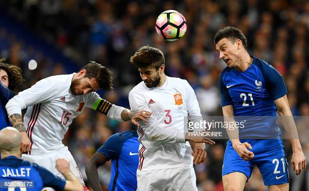 TOPSHOT Spain's defender Sergio Ramos and Spain's defender Gerard Pique vies with France's defender Laurent Koscielny during the friendly football...