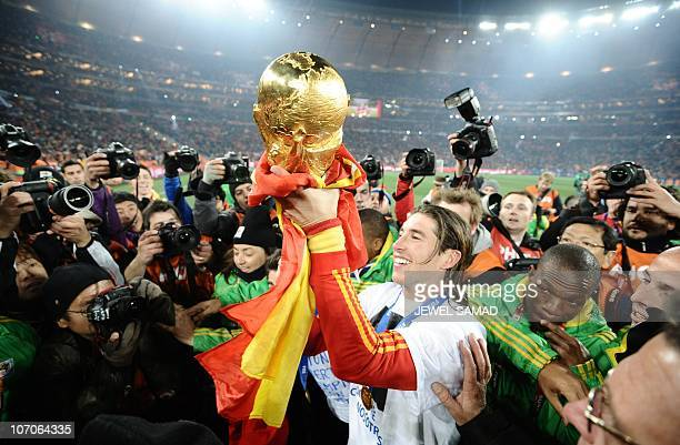Spain's defender Sergio Ramos holds up the trophy the base of it wrapped in the Spanish national flag during the award ceremony following their 2010...