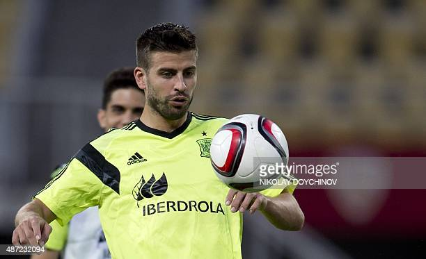Spain's Deffender Gerard Pique plays with a ball during a training session at the Filip II Arena stadium in Skopje on September 7 on the eve of their...