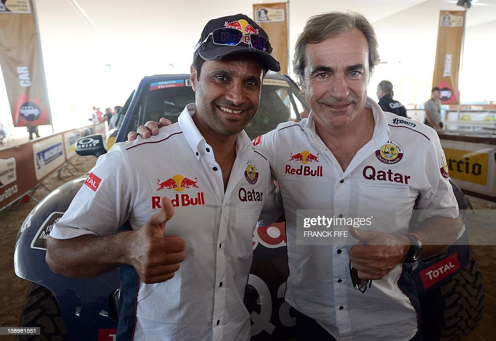 Spain's driver Carlos Sainz (R) and Qatar's driver Nasser Al-Attiyah pose in Lima on January 4, 2013, ahead of the 2013 Dakar Rally which this year will thunder through Peru, Argentina and Chile from January 5 to 20. AFP PHOTO / FRANCK FIFE