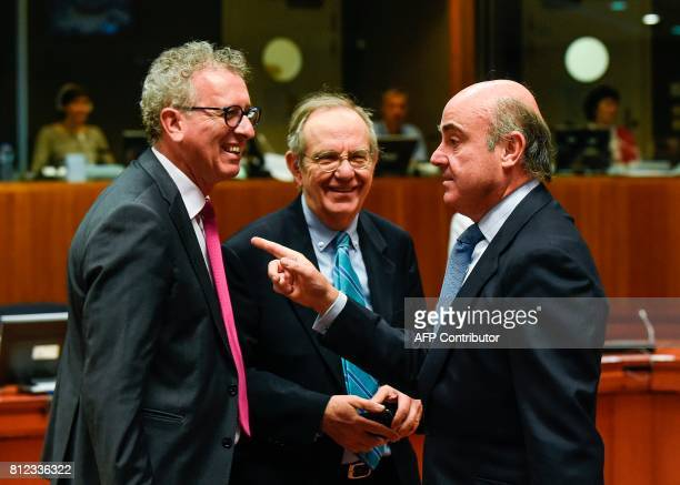 Spain's Economy Minister Luis de Guindos talks with Luxembourg's Finance Minister Pierre Gramegna and Italian Minister of Economy and Finance Pier...