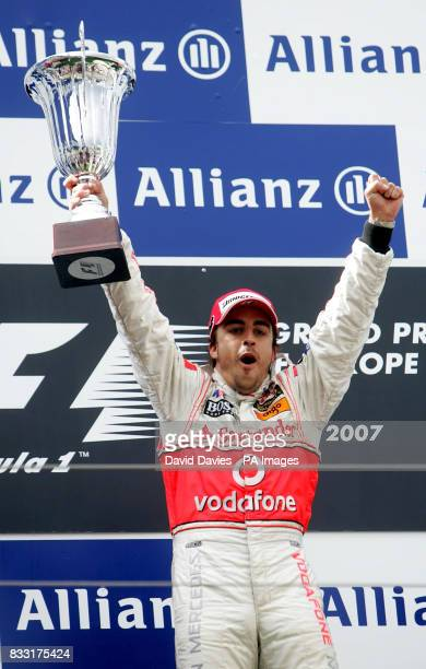 Spain's Fernando Alonso of McLaren Mercedes celebrates with the trophy after winning the European Formula One Grand Prix at Nurburgring Germany